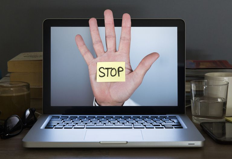 Stop hand appearing out of Laptop computer screen