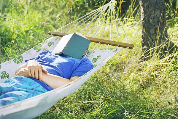 Man napping in hammock with book over face
