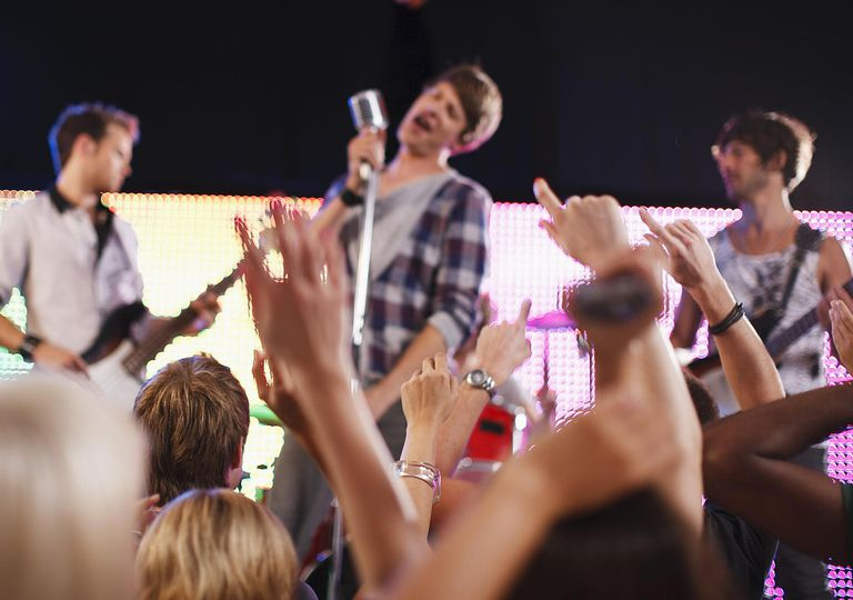 Band performing on stage, crowd in foreground