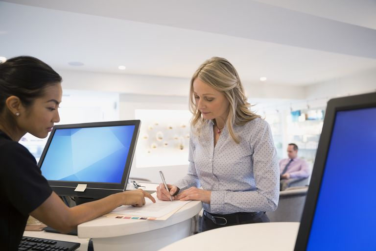 Receptionist guiding patient filling out paperwork in clinic