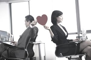 two office co-workers passing a paper heart to one another