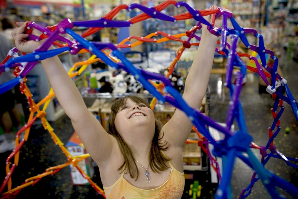 A young girl plays with a toy at a store in Rockland, Maine, USA.
