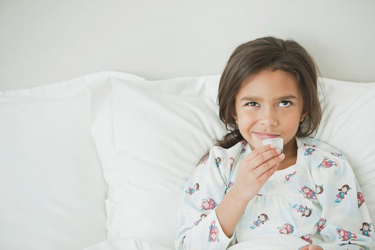 Mixed race girl laying in bed taking medicine.