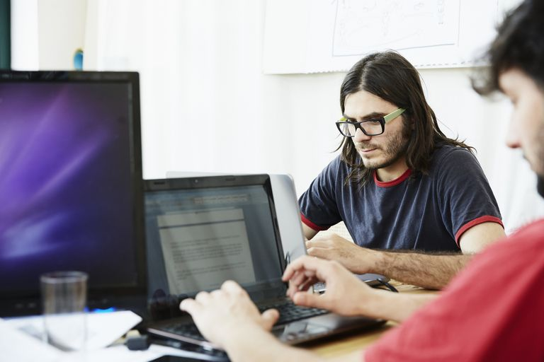 Two male office workers typing on laptops in office