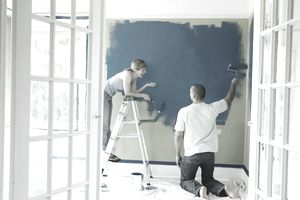 Young couple conversing while painting wall