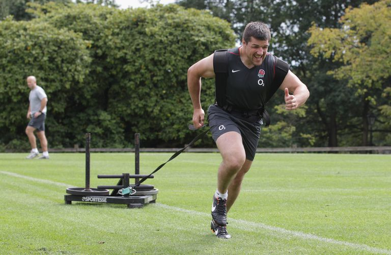 Rugby player running while pulling weighted sled