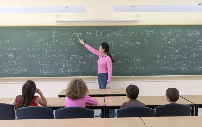 math student explaining equation at chalk board