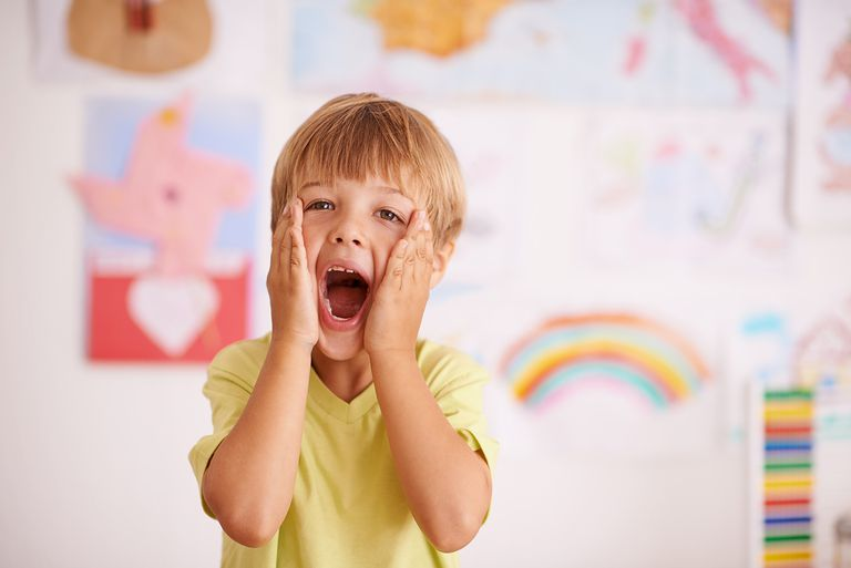 A young boy cupping his face while screaming.