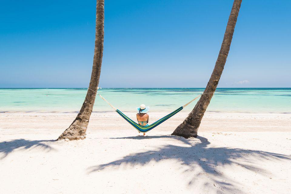 woman lying on hammock on a tropical beach.