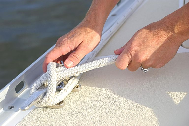 Close-up of a woman's hands as she ties a knot on a sailboat