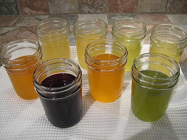 Jars of melted soy wax with several natural colors