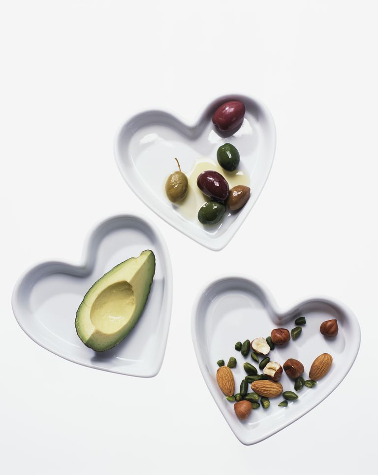 Olives , nuts and avocado in heart-shaped dishes