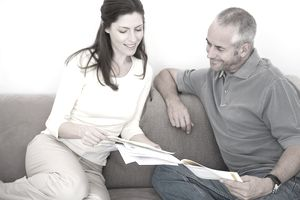 couple sitting on couch looking at paperwork