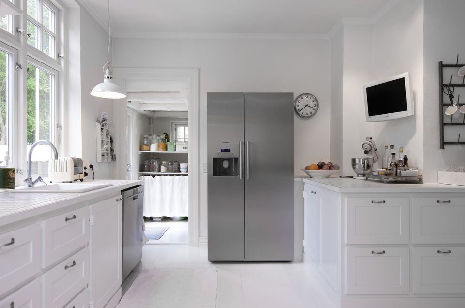 White kitchen with silver upright fridge in Hanne Davidsen home renovation, Silkesborg, Denmark.