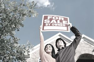 Young couple in front of home holding 'for sale' sign