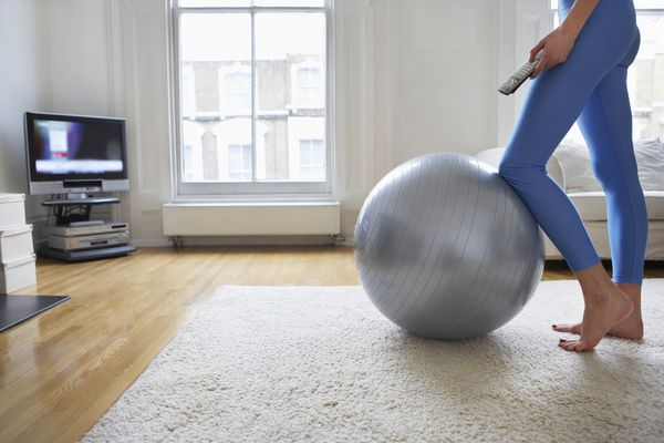 Woman with exercise ball standing in front of TV