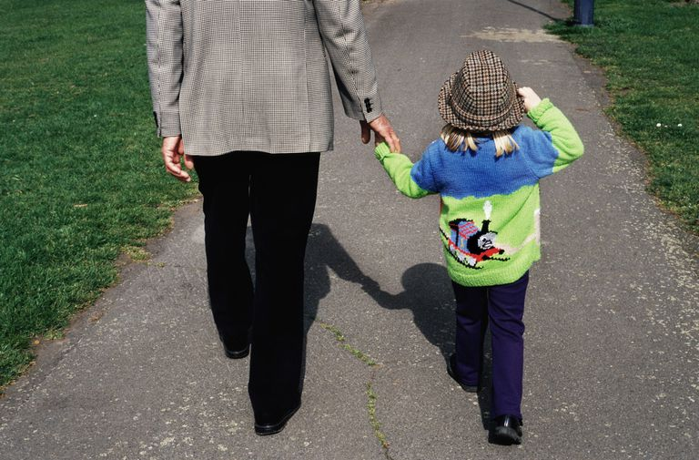 Grandfather holding hands with granddaughter, walking through park