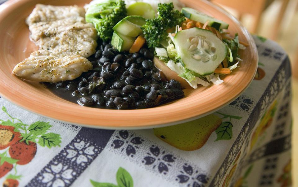 Plate of beans, fish, avocado, and veggies