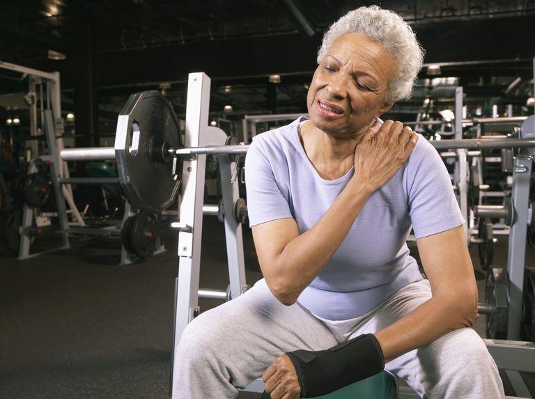 Add to Board Senior woman in gym wearing wrist strap, rubbing shoulder