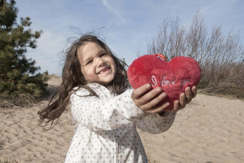 Girl offering heart-shaped pillow.