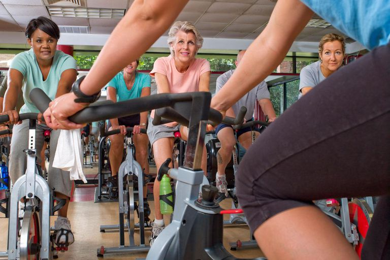Female trainer with group on exercise bikes