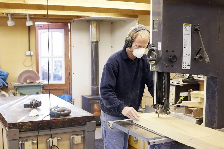 Pattern maker cutting wood with a bandsaw