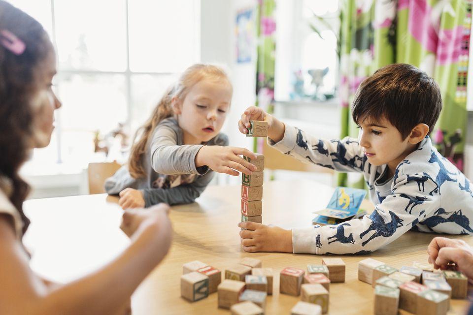 Children stacking alphabet blocks on table