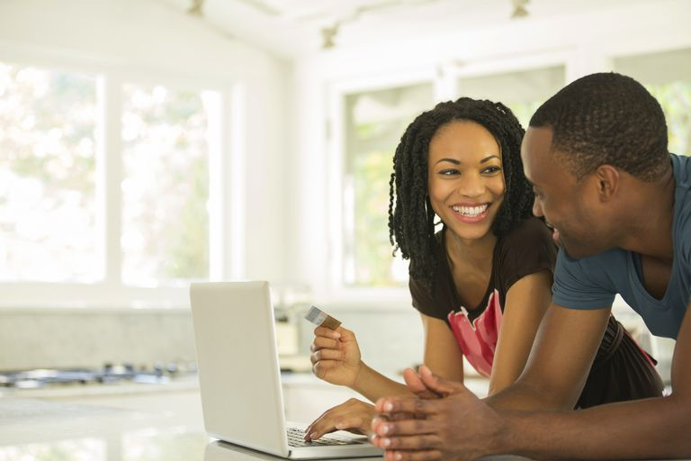 Happy couple shopping online at laptop in kitchen