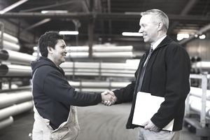 Foreman shaking hands with worker in factory