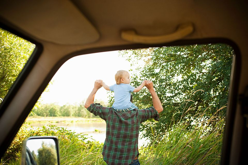 father with infant on shoulder outside of car