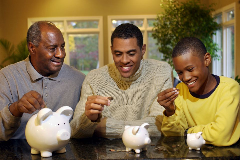 grandpa, dad, and son putting money in a piggie bank