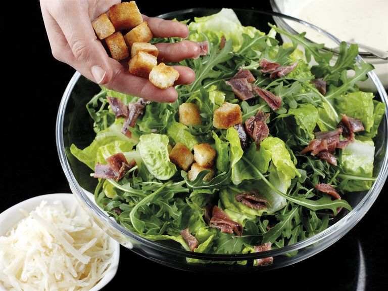 Making Caesar salad, adding croutons to mixed leaves and anchovies, bowl of grated cheese nearby