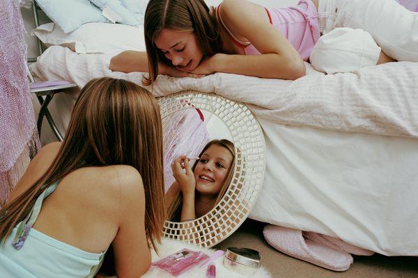 Two teenage girls using make-up in bedroom