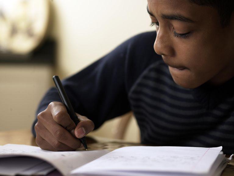 Close-up of boy (12-13) doing homework at desk