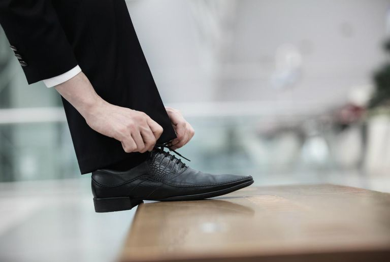 Businessman tying a shoelace