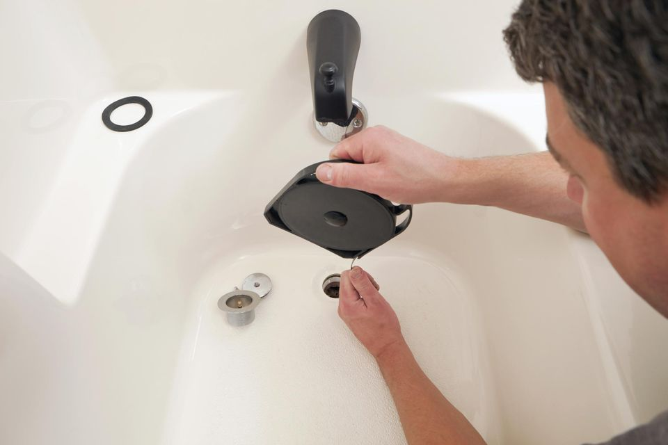 Plumber Unclogging Bathtub Drain