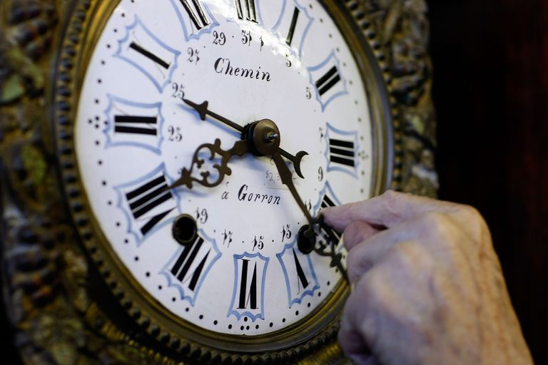 Person moving back the minute hand on an old clock