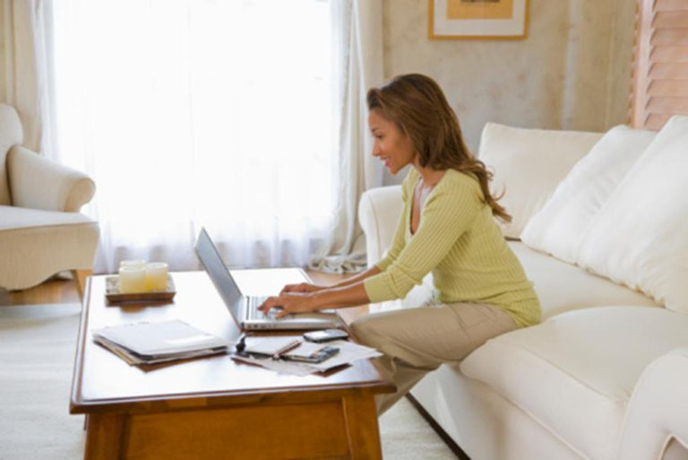 Woman sitting on sofa using laptop, side view