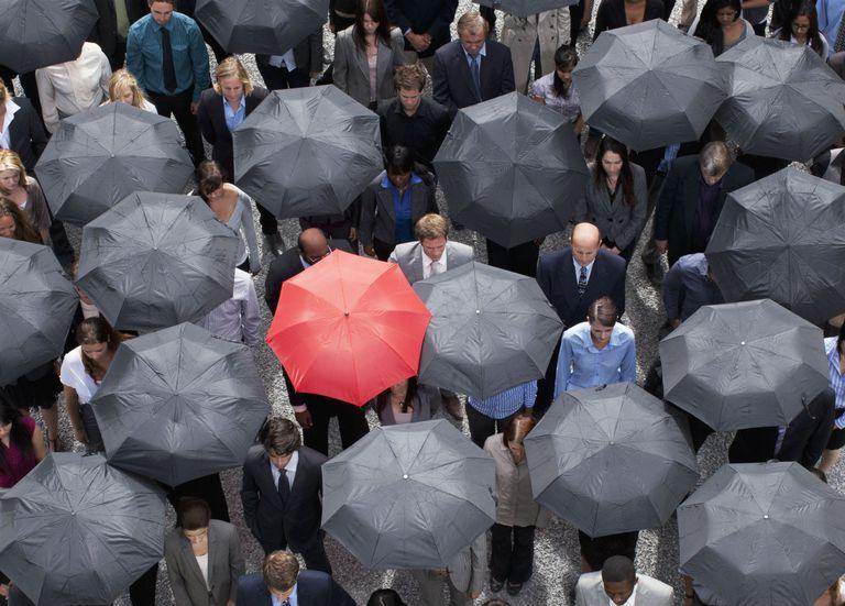 Group of black umbrellas and one red umbrella