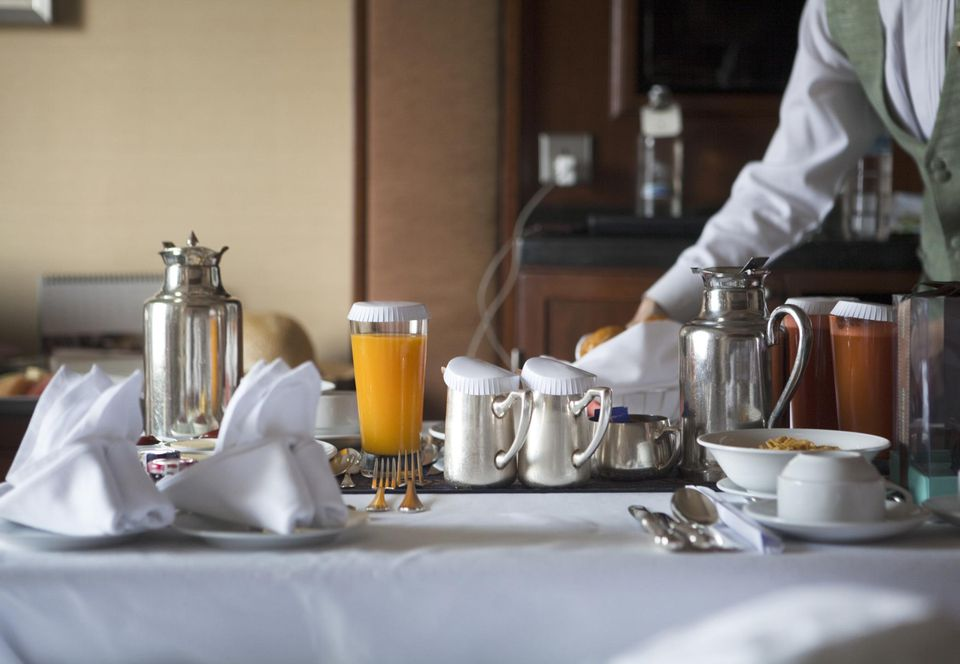 breakfast table in a hotel room with fruits and juices, coffee and tea