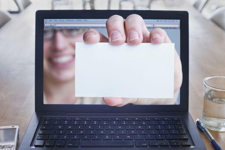 Hand holding business card coming out of laptop