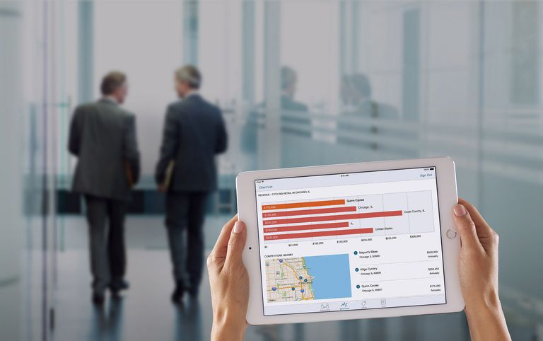 person on tablet with businessmen walking in background