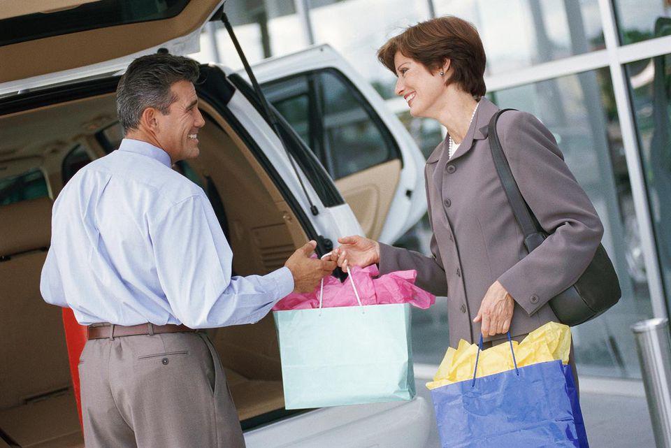 Couple loading shopping bags into mini-van