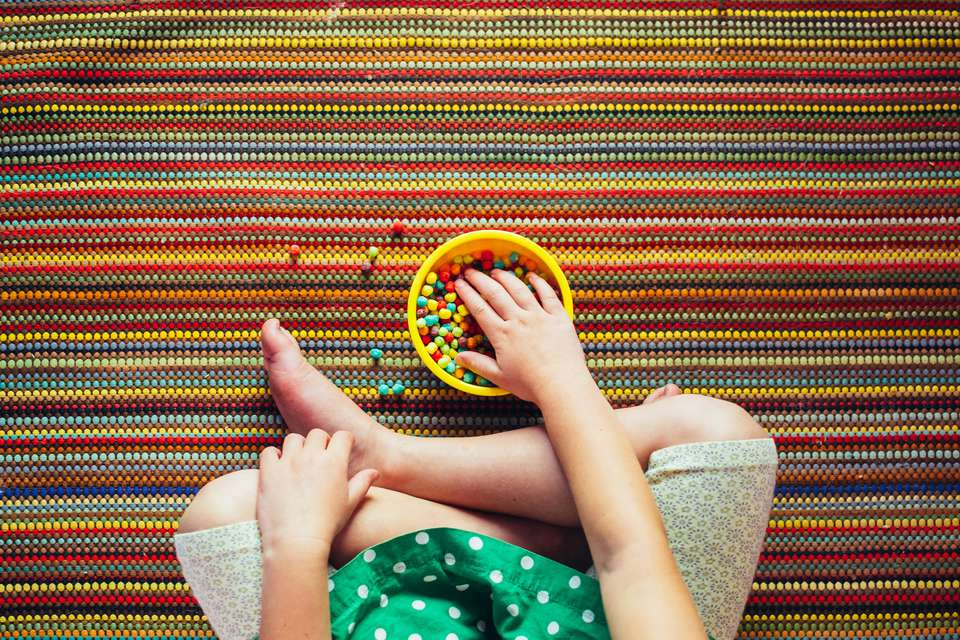 child eating candy on colorful rug
