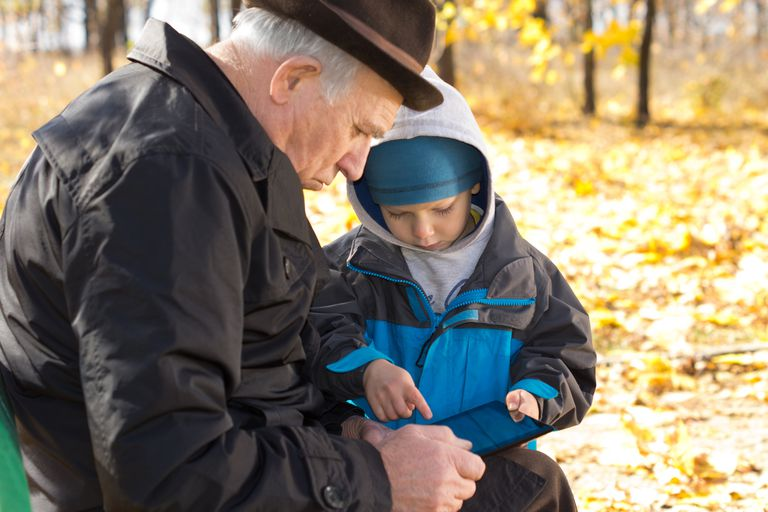 Grandfather and grandson sharing a tablet-pc