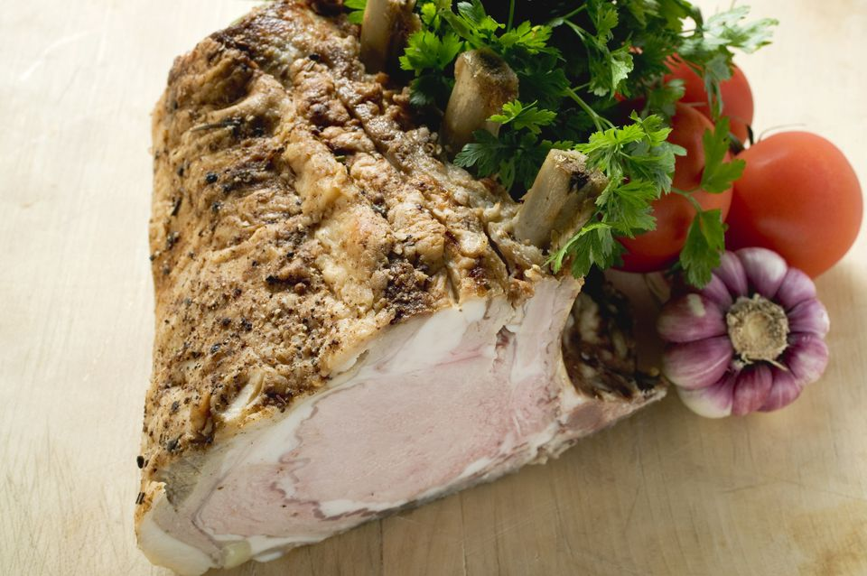 Rack of pork, garnished with parsley and fresh vegetables
