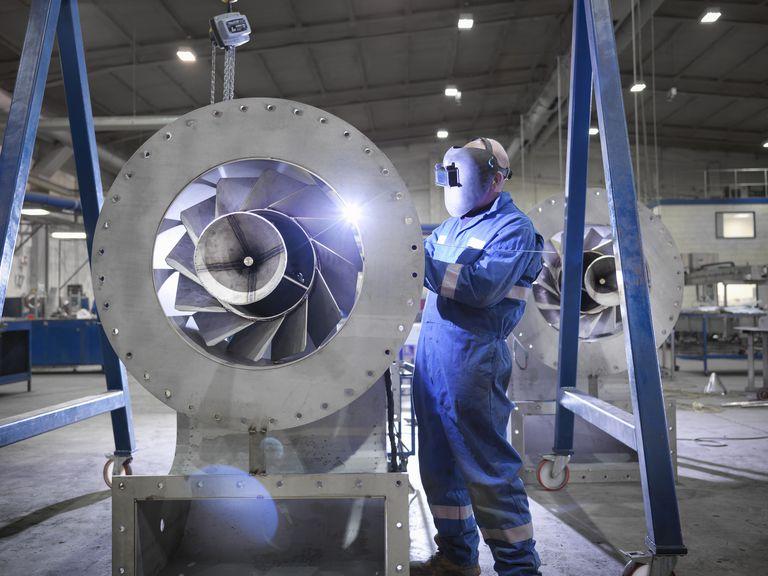 Engineer welding airduct part in engineering factory