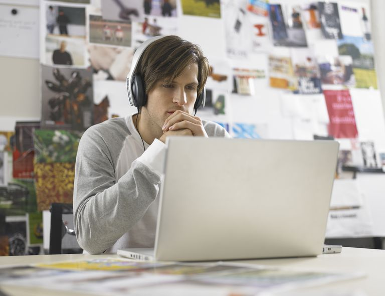Young male designer wearing headphones, using laptop, hands clasped