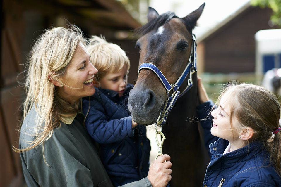 Mature woman with son and daughter petting horse