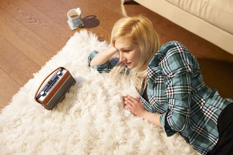 Woman relaxing and listening to radio at home.